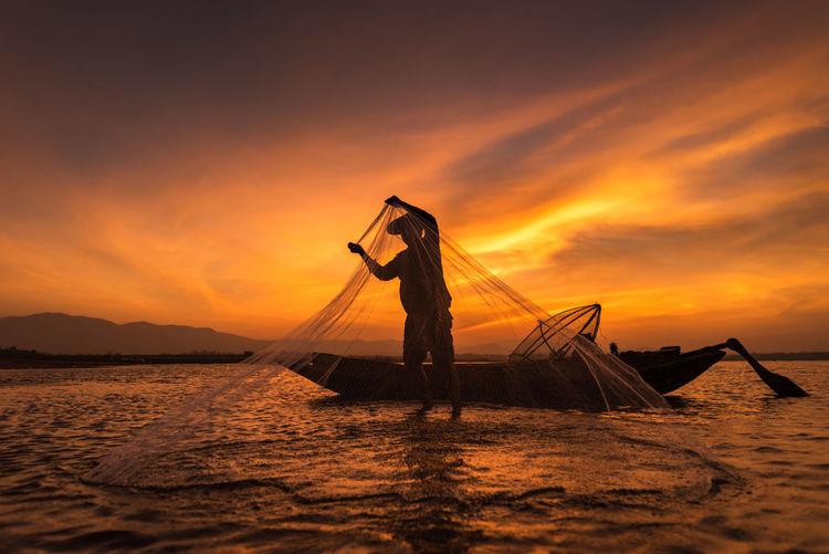 Fisherman fishing in lake against orange sky during sunset