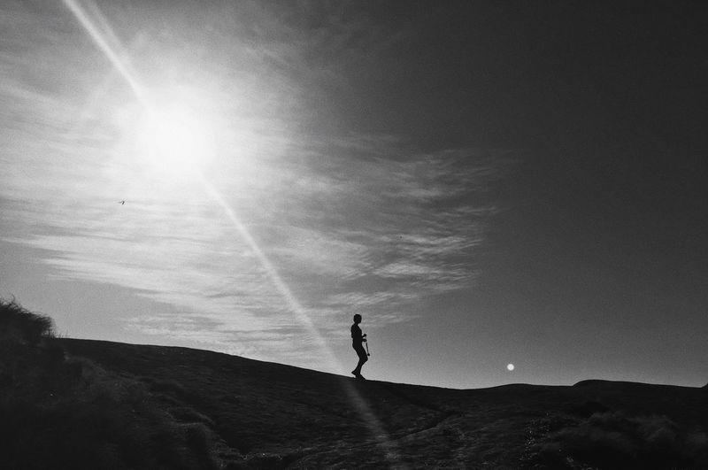 Silhouette man walking on landscape against sky