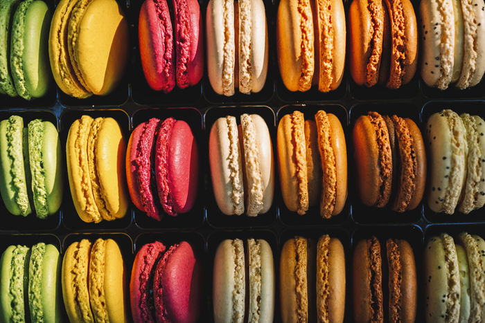 row of macaron cakes or macaroon in different colors Belgium Cookies Dessert France Green Macaroons Pink Sugar Biscuit Candy Color Colorful Confectionery Flavor Food French Macaron Many Pastel Pastry Platic Row Sandwitch Sweet Sweet Food