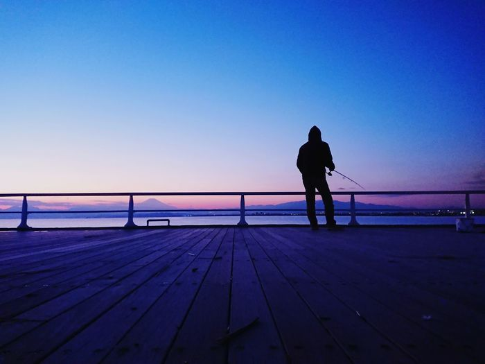 Rear view of silhouette fishing man standing against sea during sunset