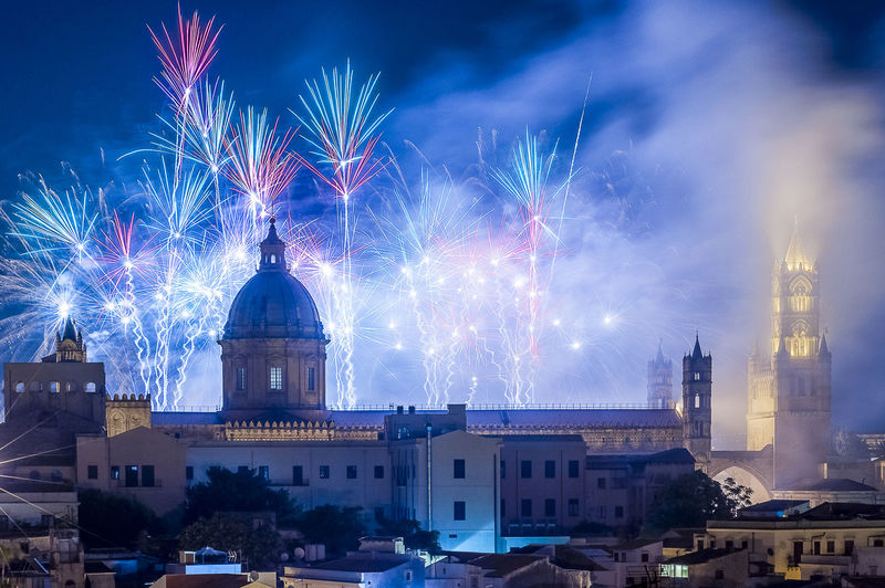 Illuminated Fireworks Over Historic Cathedral Against Sky In City At Night