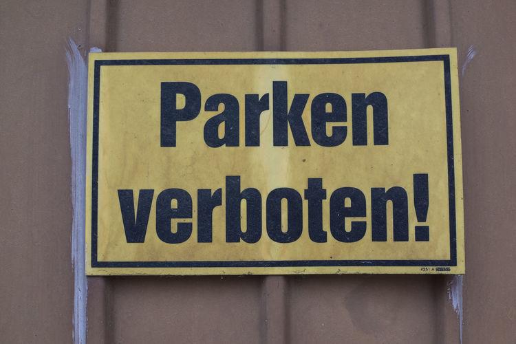 Close-up of warning sign on corrugated iron