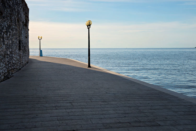 Waterfront area in sunset with old wall and shadow Beauty In Nature Concrete Day Direction Footpath Horizon Horizon Over Water Lighting Equipment Long Nature No People Outdoors Promenade Scenics - Nature Sea Sky Street Street Light The Way Forward Tranquil Scene Tranquility Water