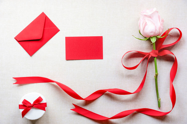 Close-up of rose and gift on table