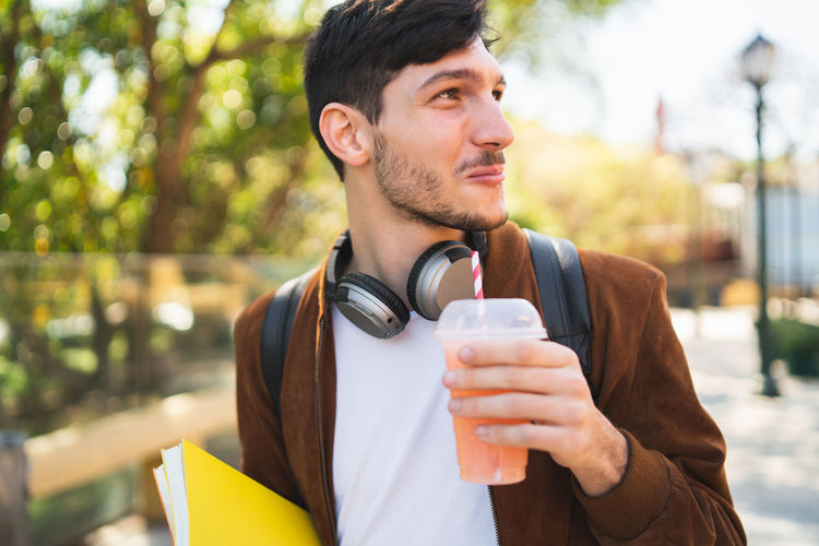 Young man drinking juice while looking away