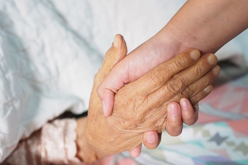 Cropped image of person holding senior woman hand at home