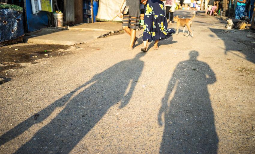 Shadow of people walking on road
