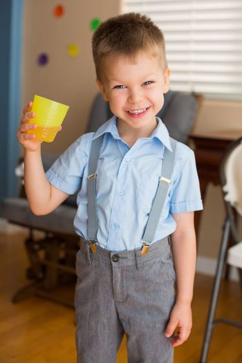 Portrait of smiling cute boy holding drink at school