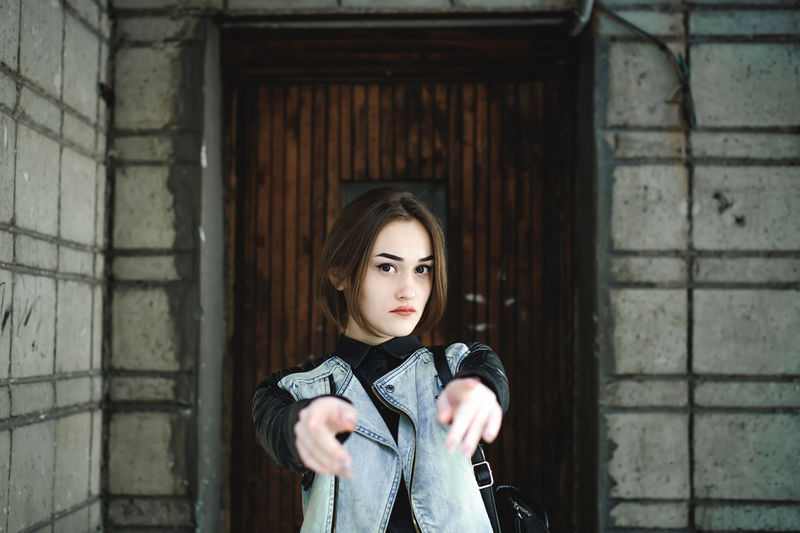 Portrait Of Young Woman Pointing Towards Camera While Standing Against Wall
