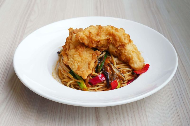High angle view of fried chicken with pasta in plate on table
