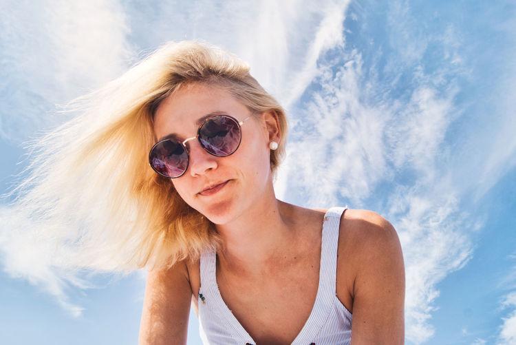 Portrait of woman wearing sunglasses against sky