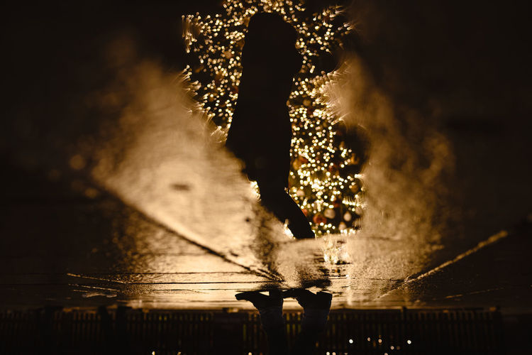 Low section of silhouette woman standing by illuminated water at night