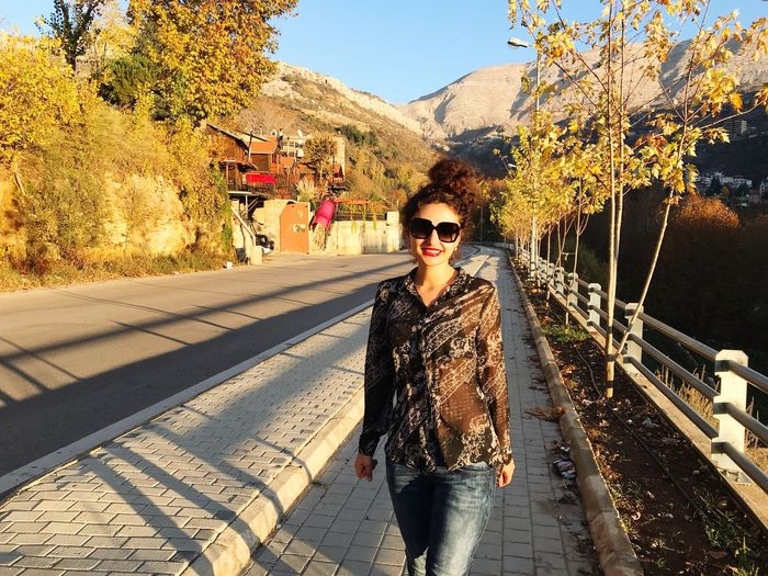 Mountain View Mountain Road Sunglasses Looking At Camera Real People Front View Young Adult One Person Young Women Outdoors Portrait Sunlight Lifestyles Leisure Activity Day Tree Standing Beautiful Woman Nature Smiling Mountain Beauty In Nature