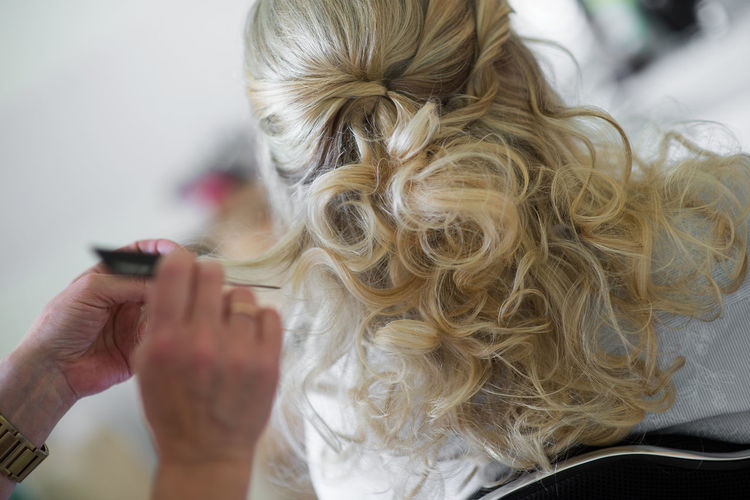 Cropped image of hairdresser styling customer hair in salon