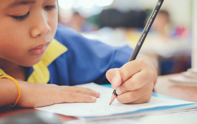 Child Real People Close-up Boys Headshot Table Holding One Person Childhood Portrait Indoors  Writing Concentration Lifestyles Focus On Foreground Paper Males  Innocence Studying Classroom School Reading Writing