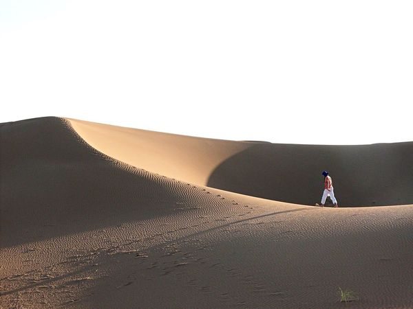 Walking in the desert at Erg Chegaga in Morocco Morocco Travel Photography Desert Edge Of The World Deserts Around The World Sand Empty Places Loneliness Desert Beauty People And Places Lost In The Landscape