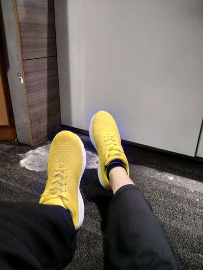 Low section of person standing on yellow shoes