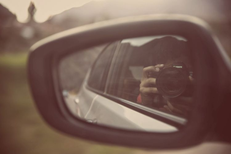Close-up portrait of woman photographing on side-view mirror