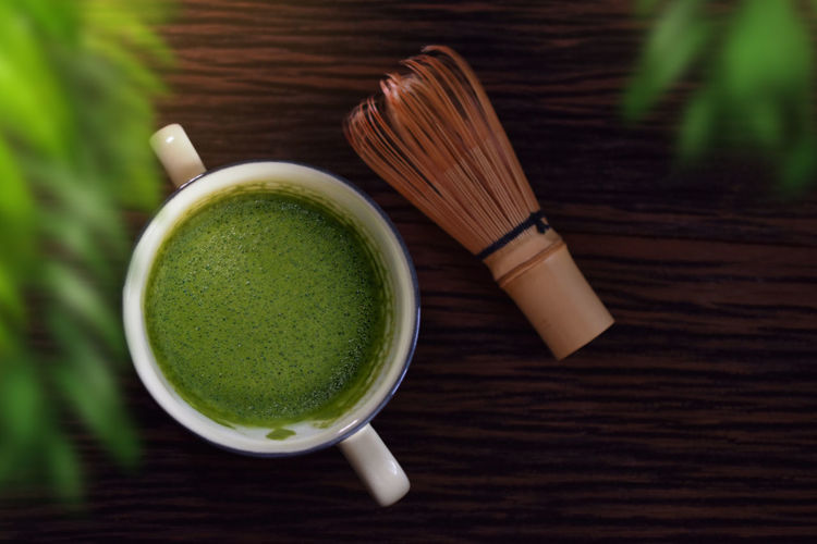 Hot Matcha Green Tea Latte Cup on Wooden Table with Chasen or Bamboo Whisk. Japanese Traditional Drink. Blurred Green Leaf as foreground. Top View Matcha Tea Green Ceremony Culture Latte Traditional Oriental Wooden Set Gourmet Asian  Ingredient Beverage Herb Whisk Top View Morning Organic Drink Leaf Freshness Cup Table Japanese  Calm Mug Chasen Classic Old Retro Hot Plant Leaves Relaxation Closeup Light Lifestyle Objects Photo Nobody Hot Drink High Angle View Still Life Close-up Tea Cup Refreshment Japanese Food