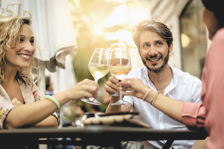 Smiling Friends Toasting Wineglasses At Restaurant