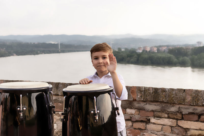 Happy kid playing bongos by the river.