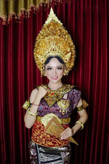 Portrait of woman wearing costume against backdrop