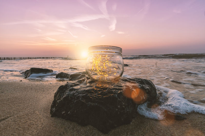 Close-Up Of Illuminated String Lights In Jar At Beach Against Sky During Sunset