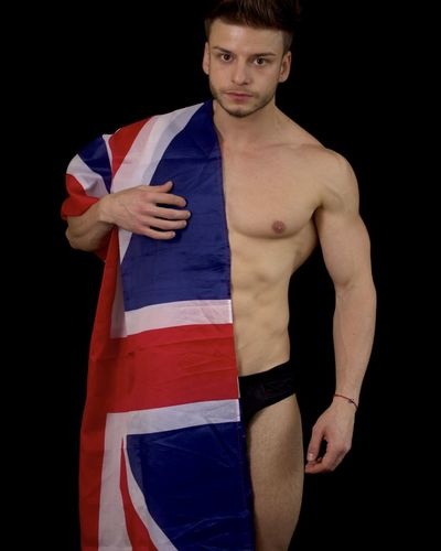 Portrait of shirtless muscular man with australian flag standing against black background