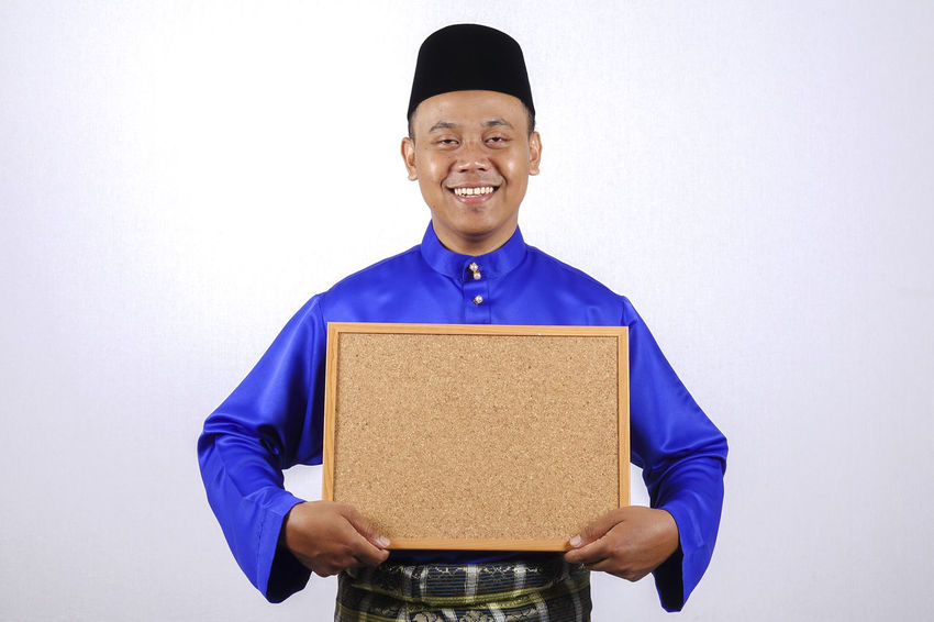YOUNG SMILING ASIAN MODEL SMILING HOLDING CHALK BOARD Baju Melayu Eid Mubarak Hari Raya Aidilfitri Adult Angpow Clothing Copy Space Cut Out Front View Happiness Holding Indoors  Looking At Camera Males  Money Packet Occupation One Person Portrait Smiling Standing Studio Shot Waist Up White Background Young Adult