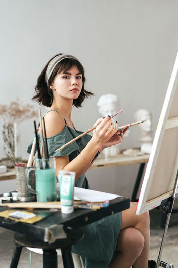 Side view portrait of confident woman holding paintbrush and palette at art studio