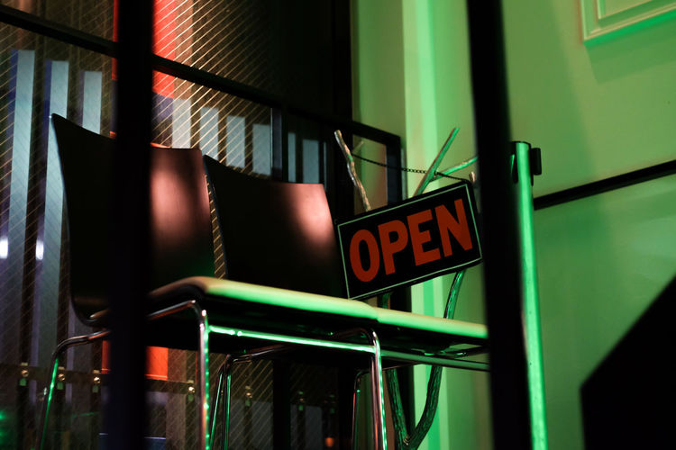 Low angle view of open sign and chairs in restaurant