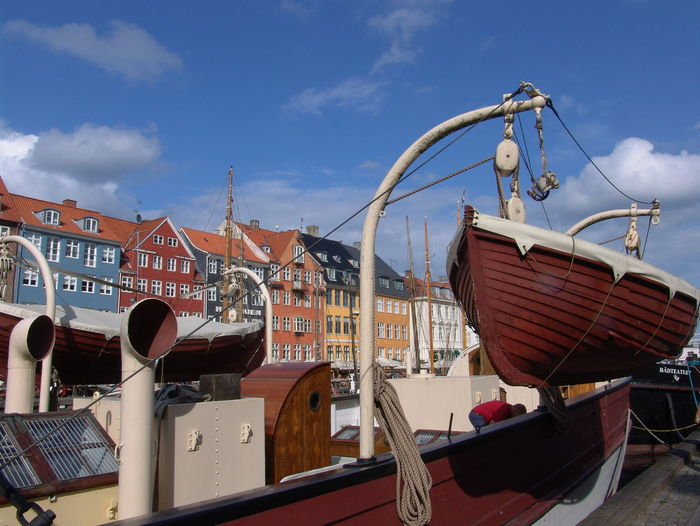 Boats moored at harbor by buildings against sky