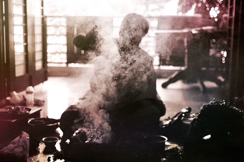 Silhouette man sitting in front of smoke at home
