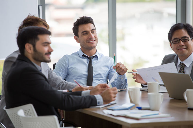 Happy colleagues sitting at office desk during meeting