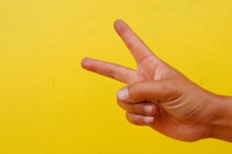 Cropped hand gesturing peace sign against yellow wall