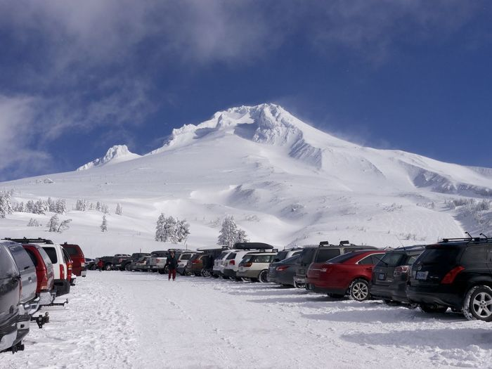 Cars parked by snowcapped mountain against sky