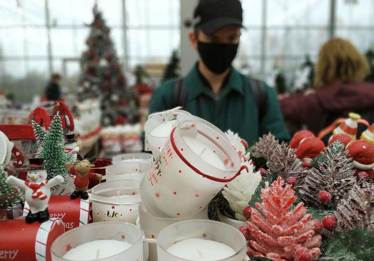 Young man wearing mask looking at christmas decoration