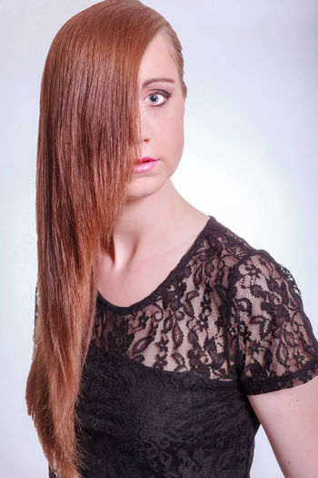 Portrait of model with long hair wearing black lace top against white background