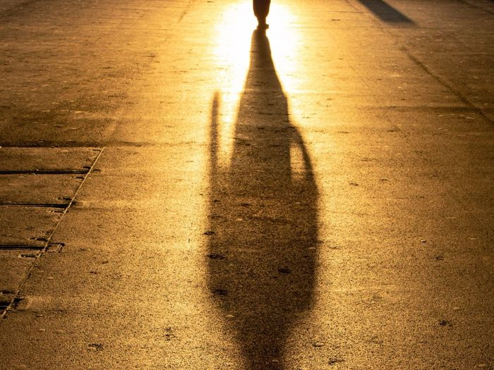 Shadow of person walking on footpath