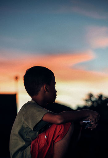 Side view of boy sitting against sky during sunset