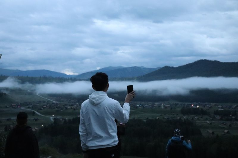 Rear view of man holding mobile phone while standing on mountain