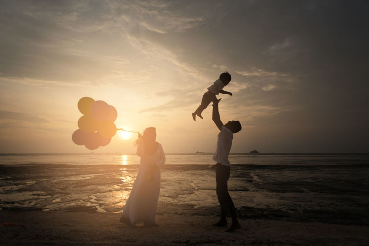 Happy family standing on shore at beach against sky during sunset
