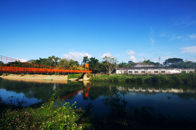 Orange steel bridge across on the river and mountain at countryside of Vangvieng,Laos Riverside Vangvieng,Laos Architecture Blue Building Building Exterior Built Structure Cloud - Sky Copy Space Countryside Day House Lake Nature Outdoors Plant Reflection Scenics - Nature Sky Steel Bridge Tranquility Tree Water