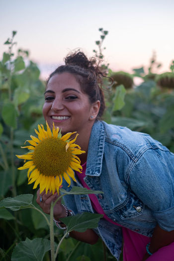 Smiling young woman with sunflower against plants