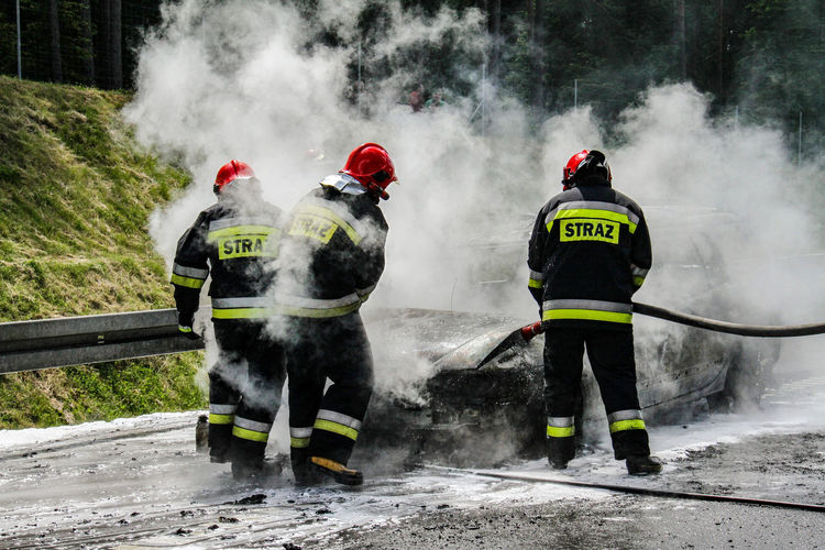 Firefighters spraying water on burning car