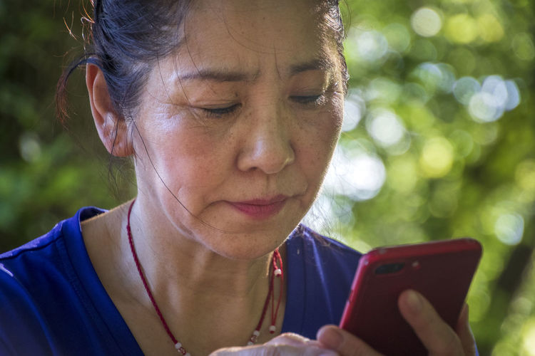 Close-up portrait of woman using smart phone outdoors