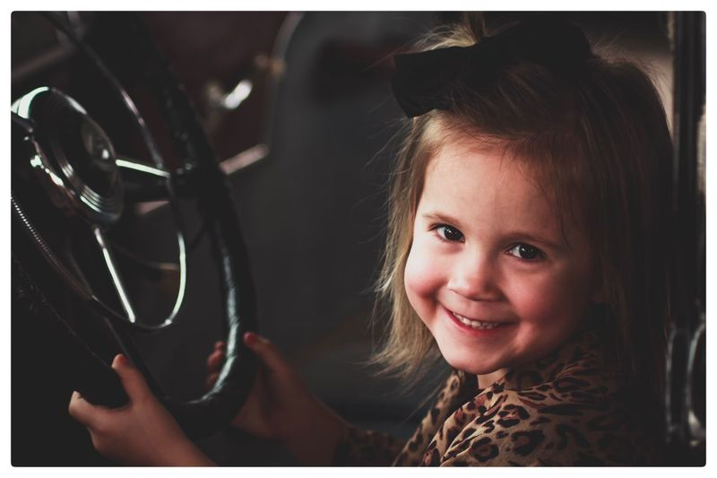 Close-up of girl smiling while sitting in car