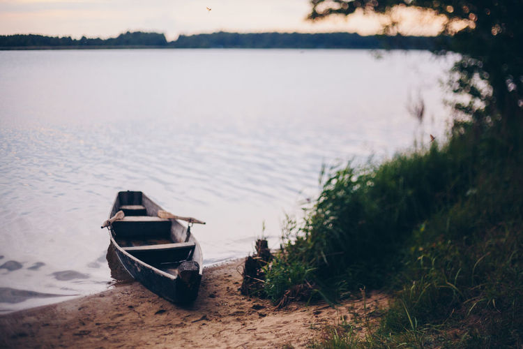 Boat moored on shore by lake
