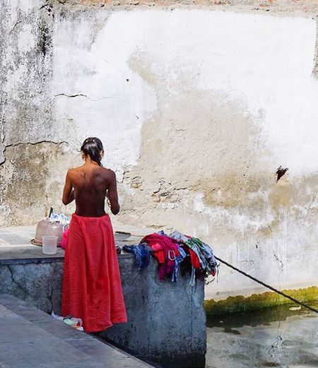 Close-up of woman sitting on wall