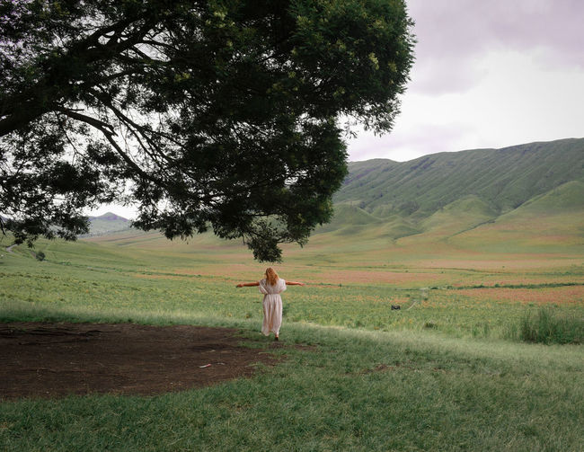 Rear View Of Young Woman With Arms Outstretched Standing On Field Against Sky